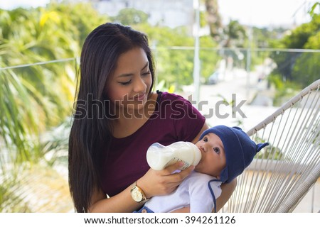 Beautiful mexican woman feeds her baby - stock photo