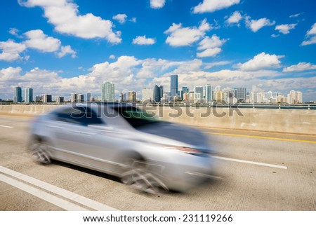 Beautiful Miami skyline along Biscayne Bay viewed from the Rickenbacker Causeway Bridge with car passing by. - stock photo