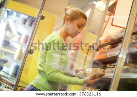 Beautiful mid adult woman shopping  in a supermarket. Horizontal shot.  - stock photo
