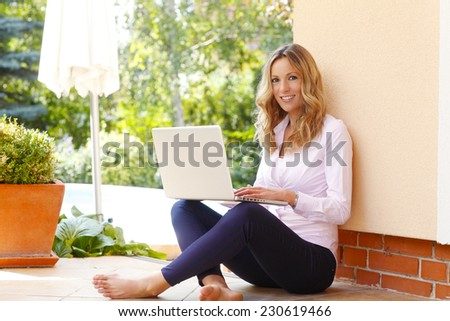 Beautiful middle age business woman sitting at garden and working on laptop.