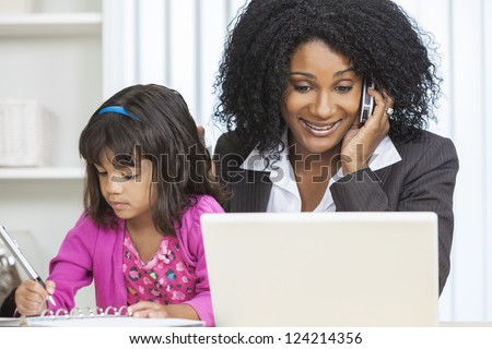 Beautiful middle aged African American woman or businesswoman working on her cell phone & laptop computer and looking after her female child daughter - stock photo