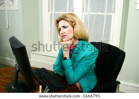 Beautiful middle aged executive business woman thinking and looking at her office computer. - stock photo