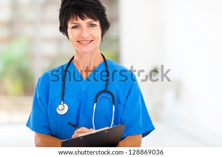 beautiful middle aged medical nurse in hospital office - stock photo