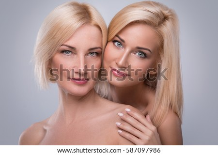 Beautiful middle aged mother and her adult daughter in studio