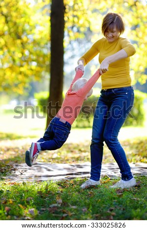 Beautiful middle aged woman and her adorable little grandson having fun in sunny park - stock photo