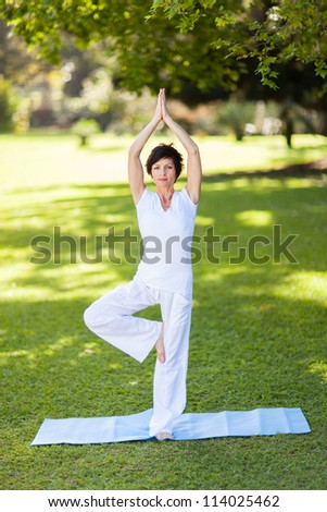beautiful middle aged woman doing yoga outdoors - stock photo
