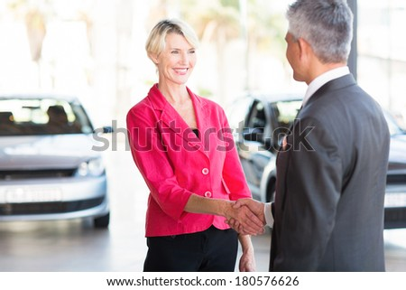 beautiful middle aged woman handshaking with car dealer - stock photo