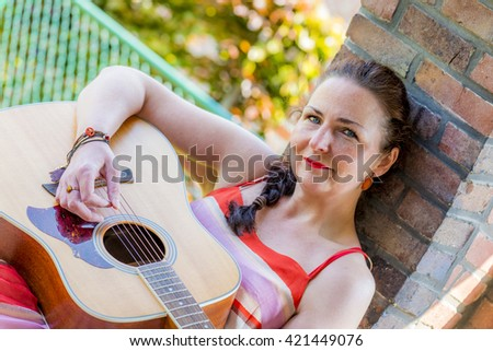 beautiful middle aged woman playing acoustic guitar