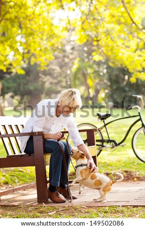 beautiful middle aged woman playing with pet dog at the park - stock photo