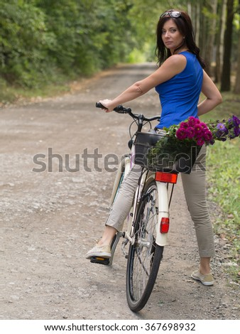 Beautiful middle aged woman posing in a walkway with her bicycle