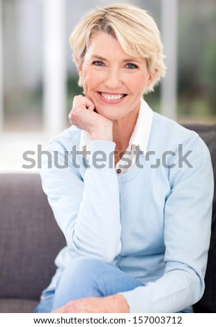 beautiful middle aged woman sitting at home - stock photo