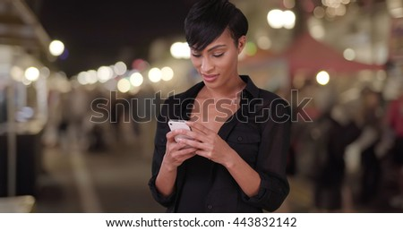 Beautiful millennial woman using smartphone texting app and making a phone call at outdoor evening farmers market