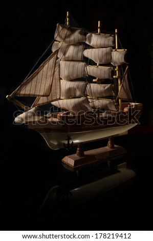 Beautiful miniature ship. Wooden ship figurine. Antique model sailing ship isolated with clipping path. Model of ship with sails on black background - stock photo