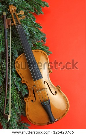 beautiful miniature violin with pine bough on red - stock photo