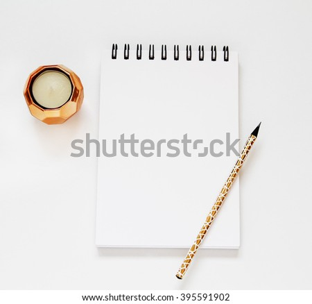 Beautiful minimalistic scene mockup. Table view above, top view. Golden candle, pencil, sheet of paper. Sketchbook styled photo mock-up - stock photo