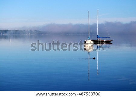 Beautiful misty morning sunrise. Landscape with a two sailing boats reflected in a calm surface of the lake and a fog over waterfront. Horizontal composition.