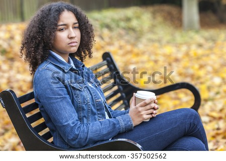 Beautiful mixed race African American girl teenager female young woman drinking takeaway coffee outside sitting on a park bench in autumn or fall looking sad depressed or thoughtful - stock photo