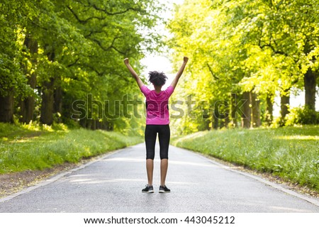 Beautiful mixed race African American young woman girl teenager fitness running jogging celebrating success on road lined with spring or summer green trees - stock photo