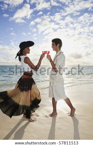 beautiful mixed race couple toast with a glass of wine at sunset on a tropical beach