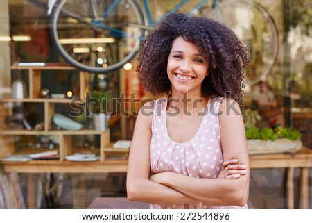 Beautiful mixed race woman standing confidently outside the front of her coffee shop   - stock photo