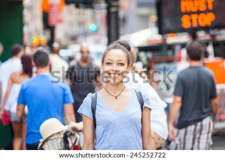 Beautiful Mixed-Race Young Woman in the City, Smiling Portrait. Unrecognizable People and Traffic on background - stock photo