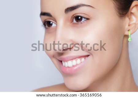 beautiful model applying cosmetic cream treatment on her face on white