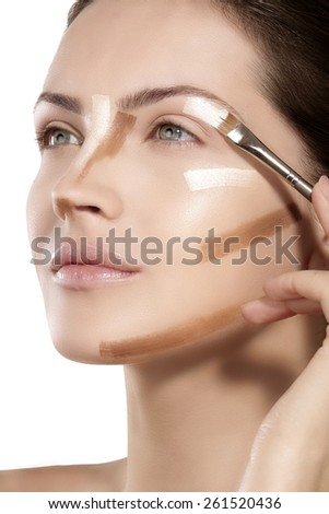 Beautiful model applying foundation with a brush on white - stock photo