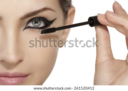 Beautiful model applying mascara on eyelashes  close up on white - stock photo