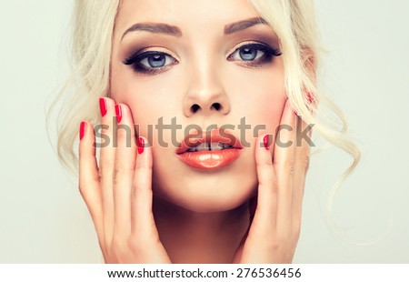 Beautiful model blonde with retro hair , bouffant hair, and a bushy tail . Hair style like Brigitte Bardot . Red nails manicure - stock photo