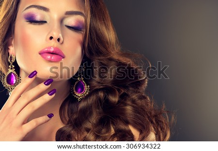 Beautiful model brunette with long curled hair. Purple manicured nails and jewelry earrings - stock photo