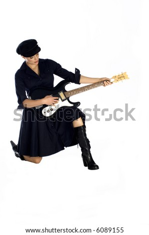 Beautiful model dressed in black dress and hat kneeling and playing a guitar