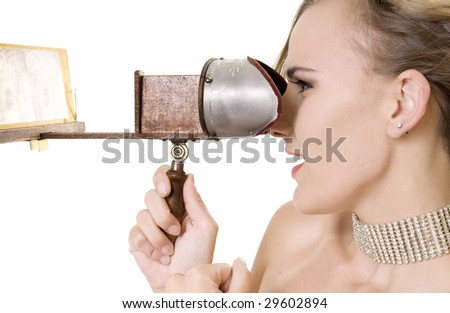 Beautiful Model Gazing at a 3D Image Through a 19th Century Stereopticon.  (images replaced with blurry images of my own.) - stock photo