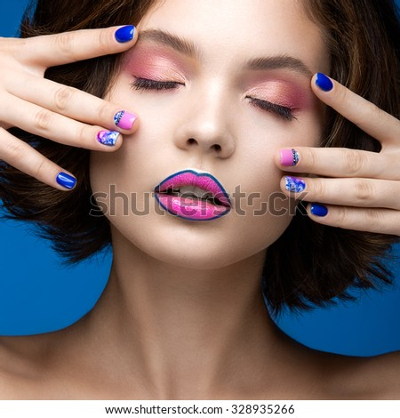 Beautiful model girl with bright makeup and colored  nail polish. Beauty face. Short colorful nails. Picture taken in the studio on a blue background.