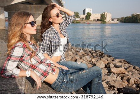 Beautiful model goes through the city on foot. Looking on the outskirts of the city.Two women looking into the distance. Undergrowth in plaid shirt and jeans  the water. Beautiful couple outdoors