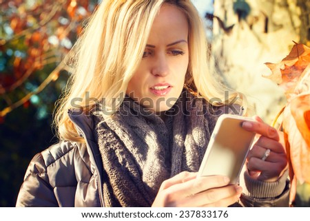 beautiful model in a park sends a message - stock photo