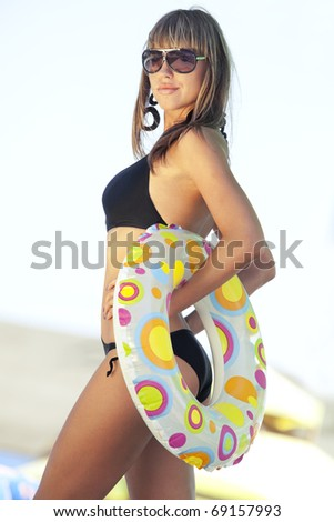 Beautiful model in black swimsuit, with multicolored inflatable ring - stock photo