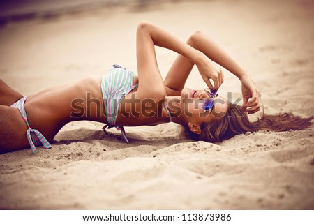 Beautiful model in sunglasses relaxing on the beach - stock photo
