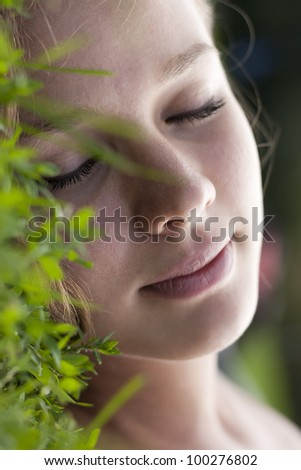 Beautiful model lying on the grass. Eyes closed.