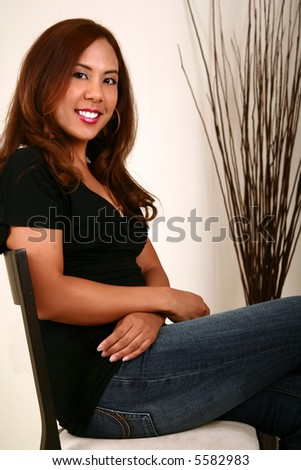beautiful model sitting on chair with big smile