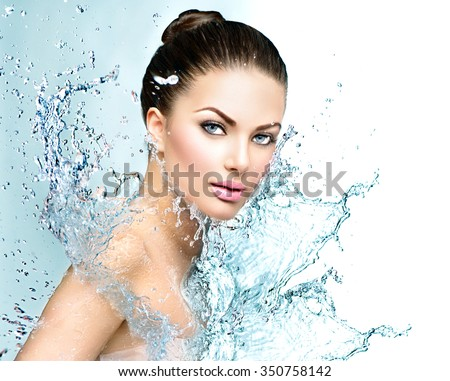 Beautiful Model Spa Woman with splashes of water. Beautiful Smiling girl under splash of water with fresh skin over blue background. Skin care, Cleansing and moisturizing concept. Beauty face - stock photo