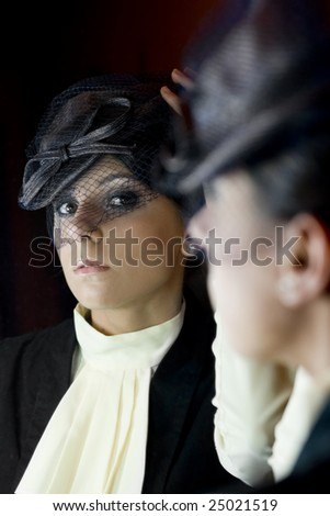 Beautiful model who is looking in the mirrow. Retro style. - stock photo