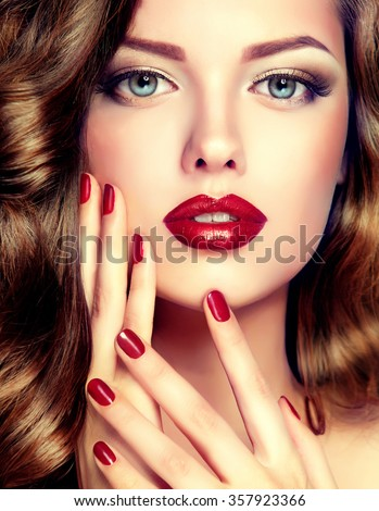 Beautiful model with curly hair and red manicure closeup . fashion trend image ,the girl with blue eyes , fashion makeup and red nails - stock photo