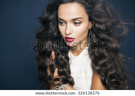 Beautiful model with elegant hairstyle . Beautiful woman with curly hairstyle and colourful makeup over blue background. Copy space for your text. Studio shot, horizontal - stock photo