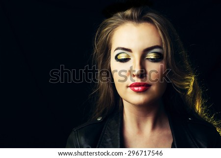 beautiful model with golden makeup against dark background - stock photo