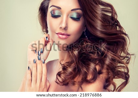 Beautiful model with long curly hair , fashion makeup and silver nails - stock photo