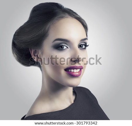 beautiful model with retro makeup and hair style against light grey studio background, isolated - stock photo