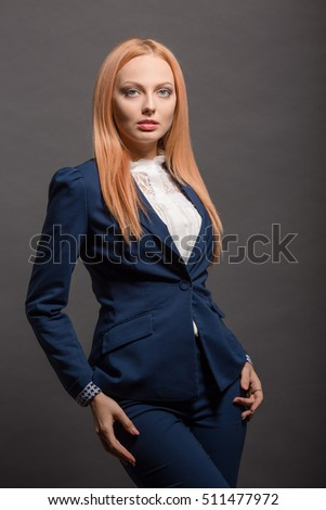 Beautiful model woman with long red hair posing for photographer while shooting for fashion or vogue magazine isolated on grey background in studio.
