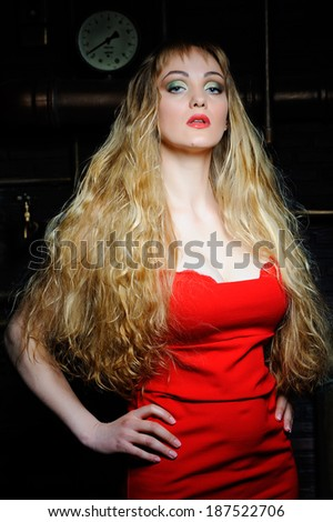 Beautiful model XL in red dress on background of pipes - stock photo