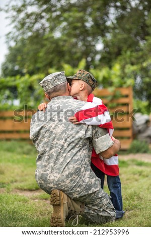 Beautiful modern american family. Father wearing military uniform hugs his son. focus on father - stock photo