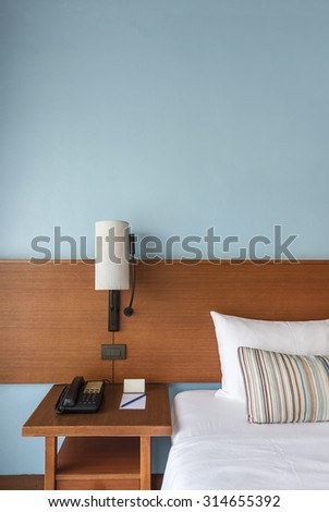 Beautiful Modern Bed with lamp and empty wall for add some text, logo, image, etc. - stock photo